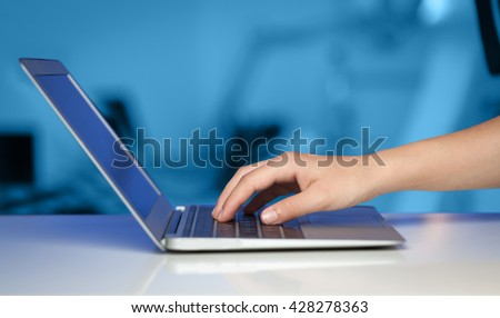 Businessman pressing modern laptop computer on colorful office background - stock photo