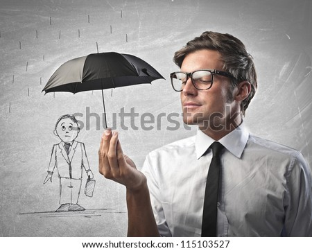 Businessman protecting with a little black umbrella a man drawn on a white wall - stock photo