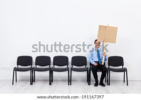 Businessman protesting alone - sitting on chairs row with blank sign - stock photo