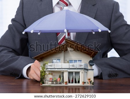 Businessman Providing Umbrella To House Model At Desk - stock photo