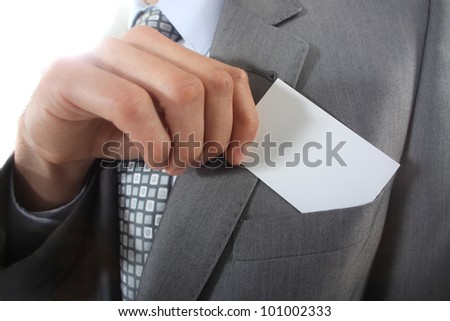Businessman pulling a business card out of his pocket - stock photo