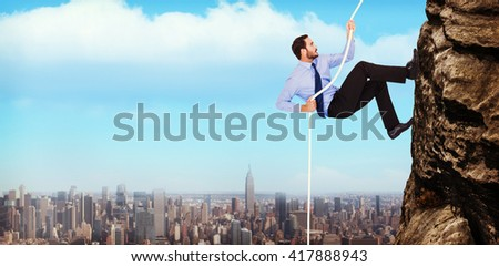Businessman pulling a rope with effort against cityscape - stock photo