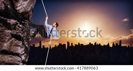 Businessman pulling a rope with effort against picture of city by sunrise - stock photo