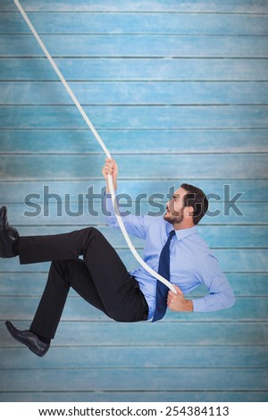Businessman pulling a rope with effort against wooden planks - stock photo