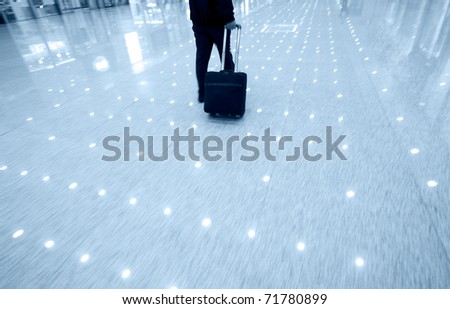 Businessman pulling a trolley luggage at station. - stock photo