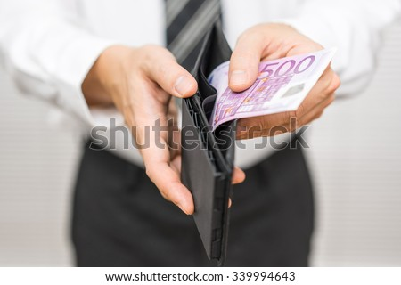 Businessman pulling 500 euro banknote  from wallet - stock photo