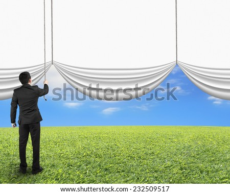 businessman pulling open blank white curtain revealed natural sky grass background - stock photo