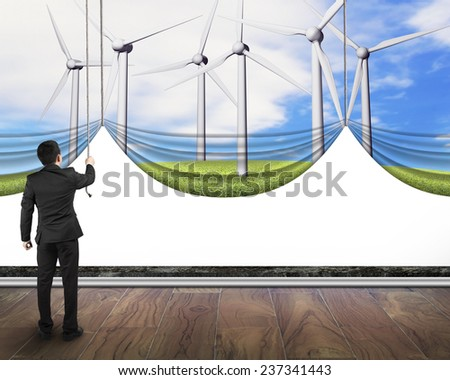 businessman pulling open group of wind turbines curtain covered blank white background, environmental protection and alternative energy concept - stock photo