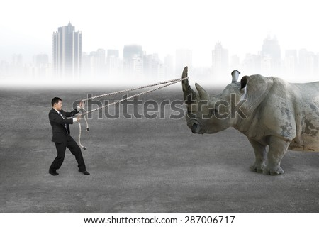 Businessman pulling rope against a huge rhinoceros on concrete floor, with cityscape skyline background. - stock photo
