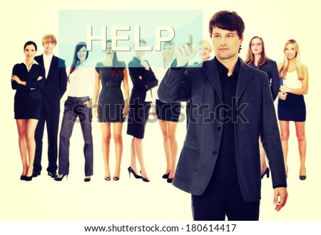 Businessman pushing HELP on a touch screen interface. Business team at background - stock photo