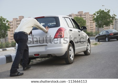 Businessman pushing his car - stock photo
