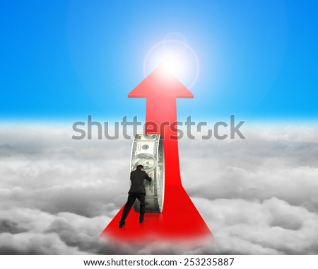 Businessman pushing money circle on red arrow with blue sky sunlight cloudscape background - stock photo