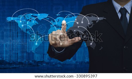 Businessman pushing world network connection center button on city tower and business graph, Elements of this image furnished by NASA - stock photo