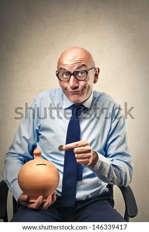 businessman puts coin into the piggy bank - stock photo
