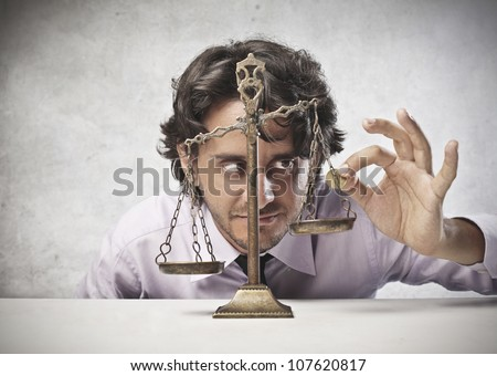 Businessman putting a coin on a balance - stock photo