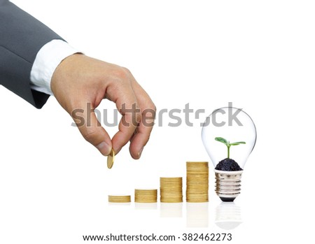 Businessman putting a coin to a stack of golden coins arranged as a graph with a green plant growing on a light bulb - Green saving concept for wealth and environment                               - stock photo
