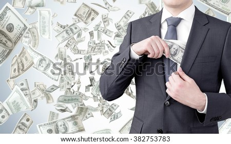 businessman putting a one-hundred dollar banknote into the chest pocket. Money flying at the background. Front view, no head. Concept of getting money. - stock photo