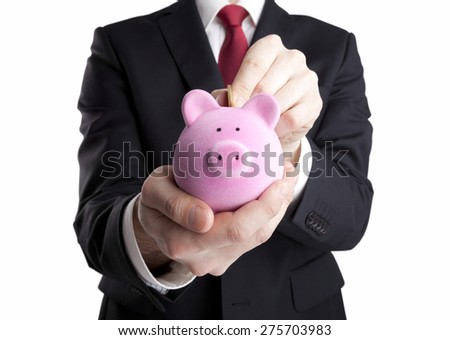 Businessman putting coin into the piggy bank isolated on white background. Clipping path included. - stock photo