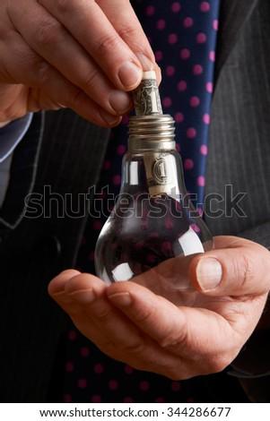 Businessman Putting Dollar Bill Into Light Bulb - stock photo