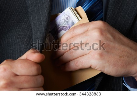 Businessman Putting Envelope Filled With Sterling In Jacket Pock - stock photo