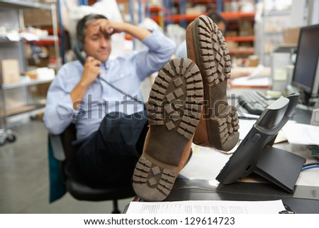 Businessman Putting Feet Up On Desk In Warehouse - stock photo