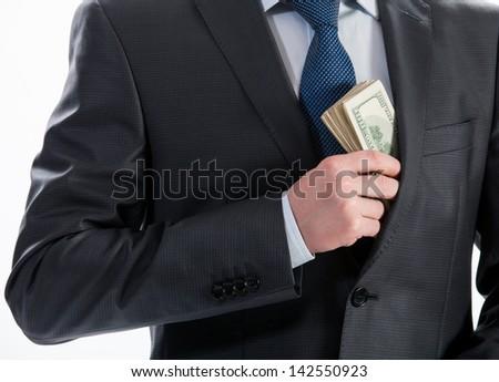 Businessman putting money in his pocket - closeup shot - stock photo
