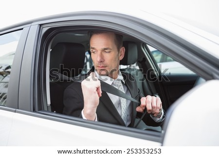 Businessman putting on his seat belt in his car - stock photo