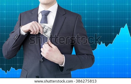 Businessman putting one hundred dollar banknotes into the chest pocket. No head seen. Blue graphs at background. Concept of getting money. - stock photo
