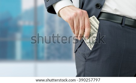 Businessman putting one hundred dollar banknotes into the pocket. Only trousers seen. Blurred office at background. Concept of winning a fortune. - stock photo