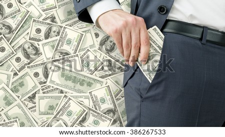Businessman putting one hundred dollar banknotes into the pocket. Only trousers seen. Dollars at background. Concept of winning a fortune. - stock photo