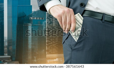 Businessman putting one hundred dollar banknotes into the pocket. Only trousers seen. Singapore at background. Concept of winning a fortune. - stock photo