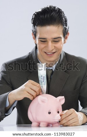 Businessman putting one hundred rupees note in a piggy bank - stock photo