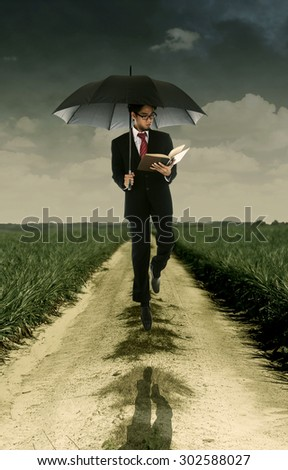 Businessman reading a book under umbrella shot outdoor - stock photo