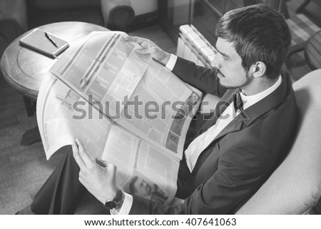 Businessman reading a newspaper at cafe, mourning. Retro revival. Black and white. Daily news. Job search - stock photo