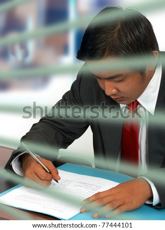 Businessman reading and signing a document - stock photo