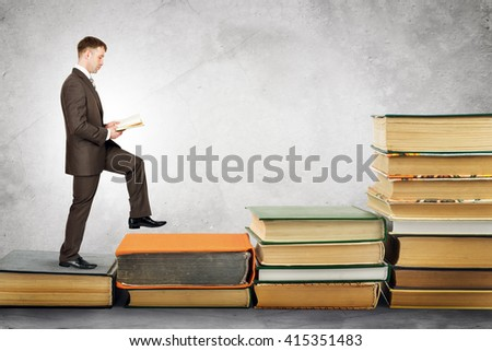 Businessman reading book and walks up stairs of books. Education concept - stock photo