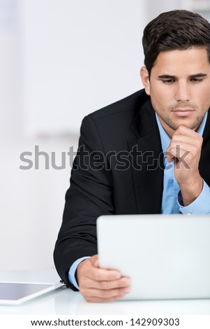 Businessman reading interesting news on his laptop sitting looking at the screen with an earnest expression, partial closeup portrait - stock photo