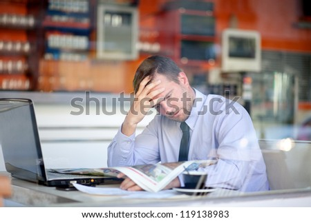 Businessman reading newspaper in a cafe - stock photo