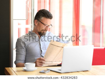 Businessman reading newspaper in cafe - stock photo