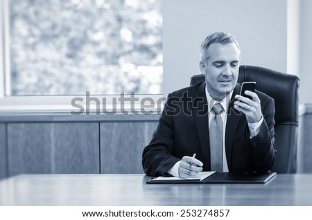 Businessman reading text messages on his phone  - stock photo