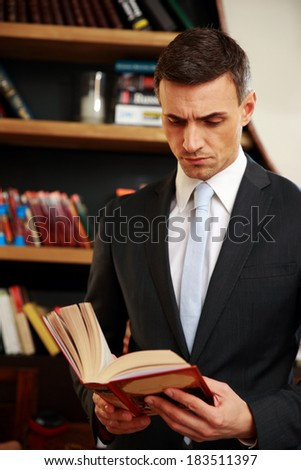 Businessman reading the book in library - stock photo