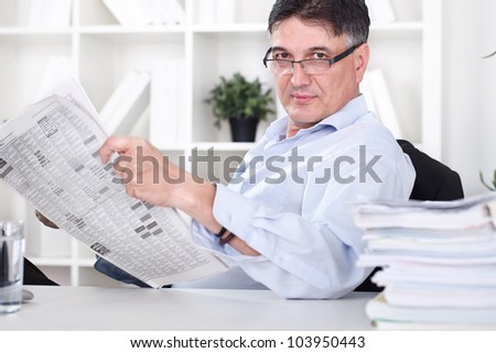 businessman reading the newspaper and having a coffee in office - stock photo
