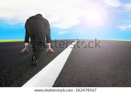 Businessman ready to run on asphalt road with white line and sky clouds sunlight background - stock photo