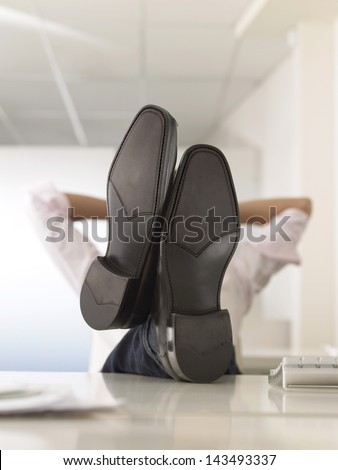 Businessman reclining with his feet up on desk in office - stock photo