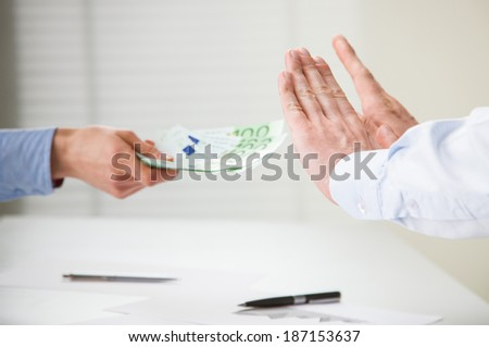 Businessman refusing to take a bribe, closeup shot of hands over the table - stock photo