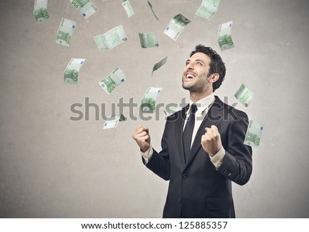 Businessman rejoicing for his success with hundred-euro banknotes flying in the air - stock photo