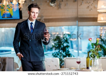 Businessman relaxing after work. Young man businessman in formal wear standing in a restaurant while holding a glass of wine and looking at the camera - stock photo