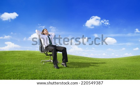 businessman relaxing on the field - stock photo
