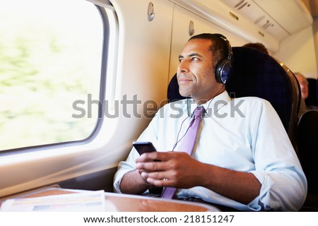 Businessman Relaxing On Train Listening To Music - stock photo