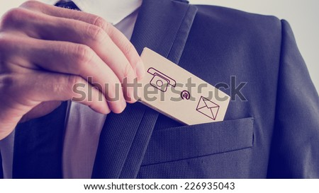 Businessman removing a wooden card with contact icons from the pocket of his suit jacket, vintage effect toned image. - stock photo